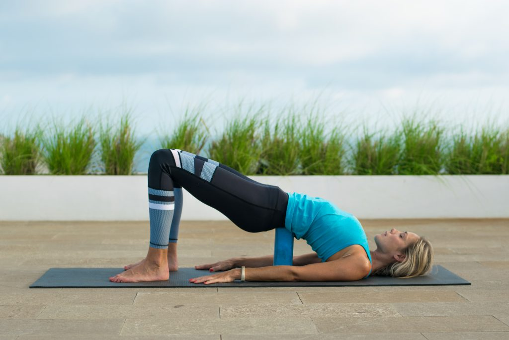 Supported Bridge is a restorative backbend that helps to release tight hamstrings.